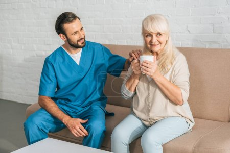 smiling caregiver looking at happy senior woman drinking tea