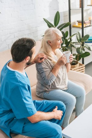 high angle view of social worker looking at smiling senior woman drinking tea