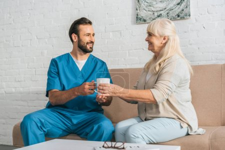smiling male nurse giving cup with hot beverage to happy senior woman