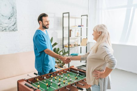 Photo for High angle view of smiling senior woman and caregiver shaking hands above table football - Royalty Free Image