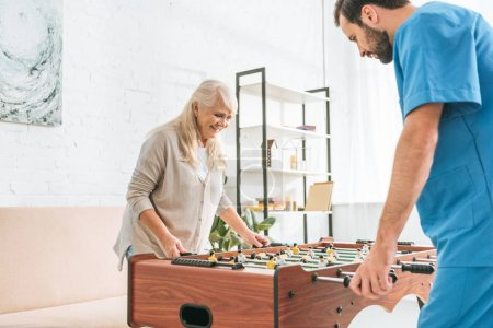 smiling senior woman and young social worker playing table football together