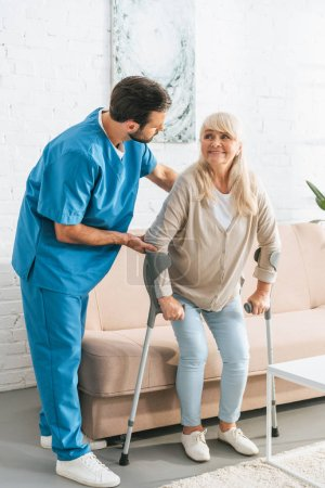 male nurse supporting smiling senior woman with crutches