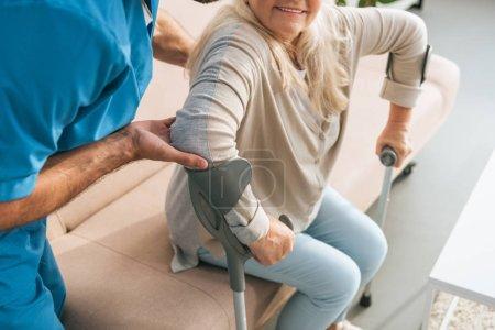 Photo pour Plan recadré de l'infirmière masculine soutenant la femme âgée avec des béquilles - image libre de droit