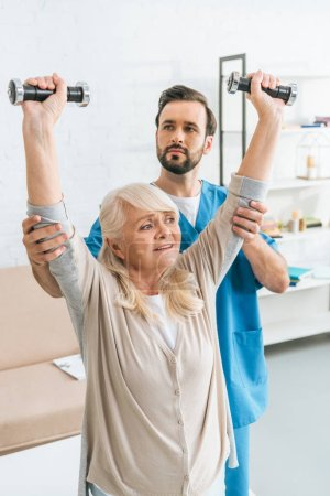 social worker helping smiling senior woman training with dumbbells