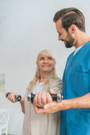 smiling social worker helping happy senior woman exercising with dumbbells