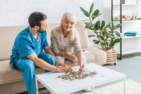 caregiver looking at smiling senior woman playing with jigsaw puzzle pieces