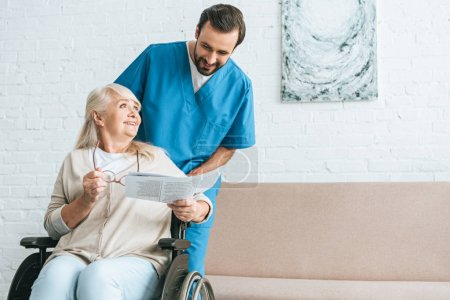 smiling young male nurse looking at happy senior woman reading newspaper in wheelchair