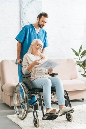 male nurse pushing wheelchair with smiling senior woman reading newspaper