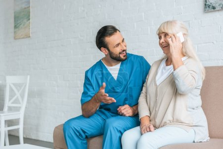 smiling male nurse looking at happy senior woman talking by smartphone