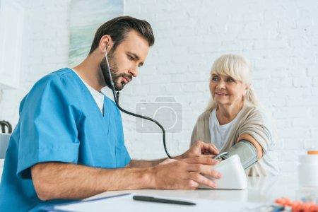 Photo pour Vue à faible angle de l'infirmière masculine mesurant la pression artérielle à la femme âgée souriante - image libre de droit