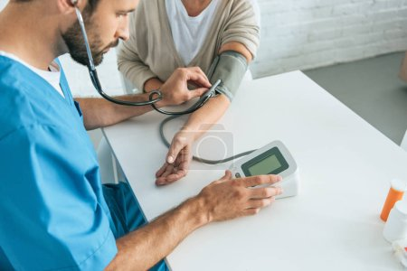 cropped shot of male nurse in stethoscope measuring blood pressure to senior woman