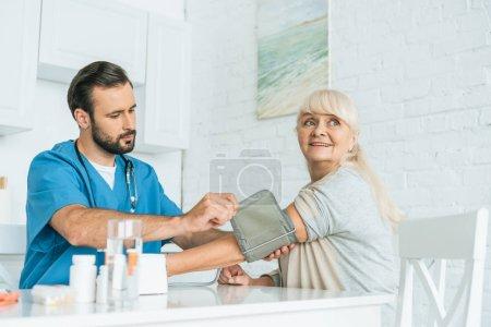 male nurse measuring blood pressure to smiling senior woman