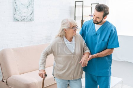 Photo for Male nurse supporting senior woman in eyeglasses with walking stick - Royalty Free Image