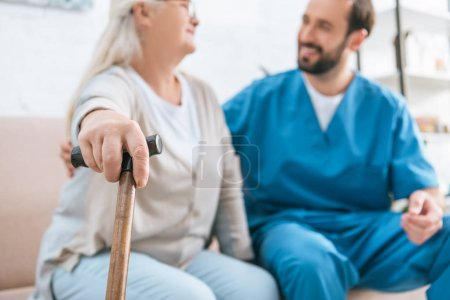 close-up view of senior woman holding walking cane and looking at smiling male nurse