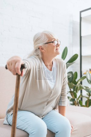 senior woman in eyeglasses holding walking cane and looking away while sitting on sofa