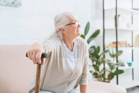 senior woman in eyeglasses holding walking stick and looking away while sitting on couch