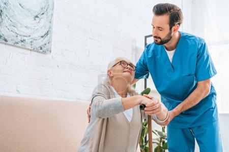 Photo pour Jeune travailleur social masculin soutenant la femme âgée dans des lunettes avec bâton de marche - image libre de droit