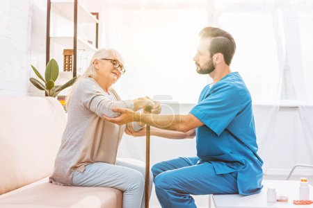side view of male nurse supporting senior woman with walking cane