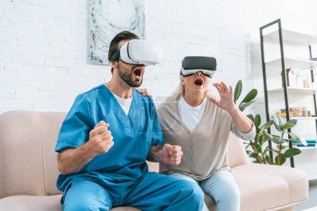 Foto de Trabajador social emocional y excitada mujer senior con auriculares de realidad virtual - Imagen libre de derechos
