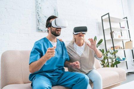 Photo pour Heureuse femme senior et jeune infirmier à l'aide de casques de réalité virtuelle - image libre de droit
