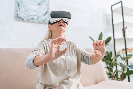 Foto de Vista de ángulo bajo de la sonriente mujer senior con casco de realidad virtual en casa - Imagen libre de derechos