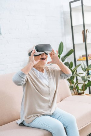 excited senior woman using virtual reality headset at home