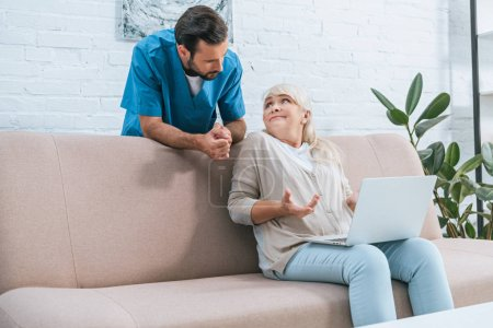 young male nurse leaning at couch and looking at senior woman using laptop