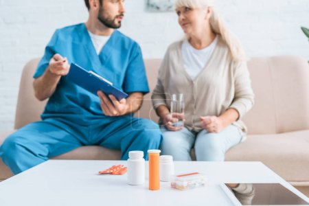 close-up view of containers with pills and digital tablet on table, male nurse and senior woman sitting on couch behind