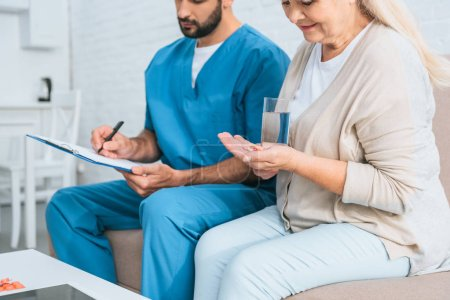 cropped shot of senior woman taking medicine and male nurse writing on clipboard