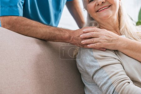 cropped shot of smiling senior woman holding hand of caregiver