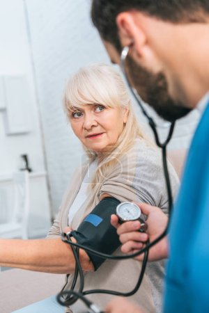 selective focus of social worker measuring blood pressure to senior woman