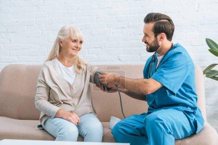 smiling male nurse measuring blood pressure to senior woman