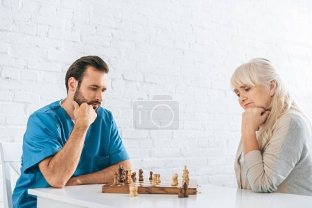concentrated senior woman and young social worker playing chess together