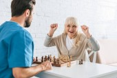 triumphing senior woman celebrating victory and looking at young social worker after chess game