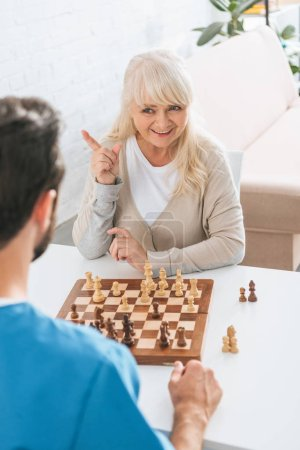 smiling senior woman playing chess with young male social worker