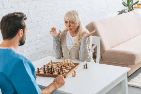 shocked senior woman playing chess with young social worker