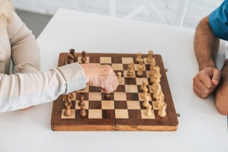 close-up partial view of senior woman playing chess with social worker