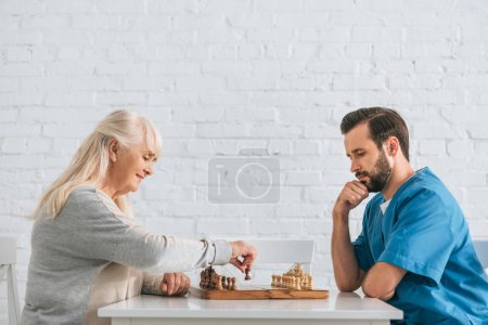 side view of young male social worker playing chess with senior woman