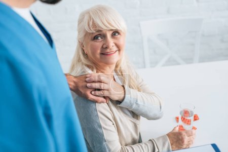 smiling senior woman taking medicine and holding hand of caregiver