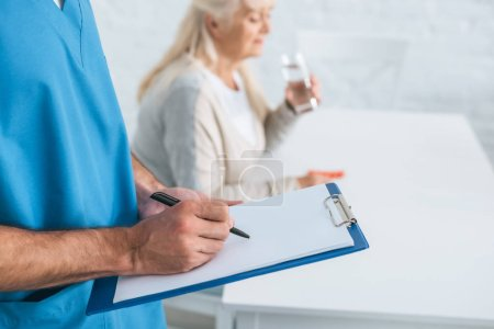 Photo for Close-up partial view of caregiver writing on clipboard while senior woman taking medicine - Royalty Free Image