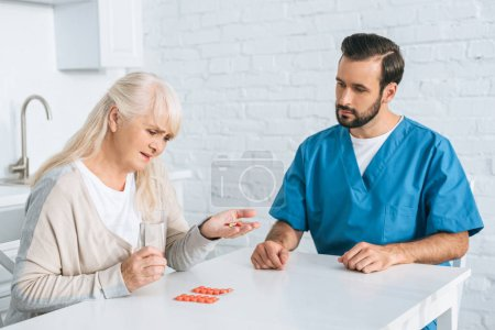 caregiver looking at diseased senior woman taking medicine