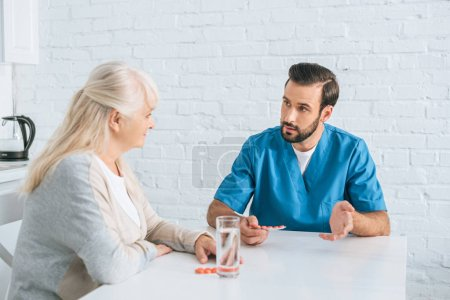 young male nurse holding pills and looking at senior woman