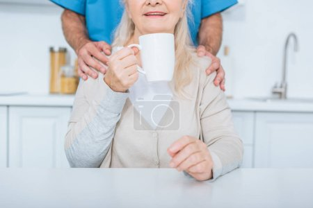 cropped shot of social worker standing near senior woman drinking tea in kitchen
