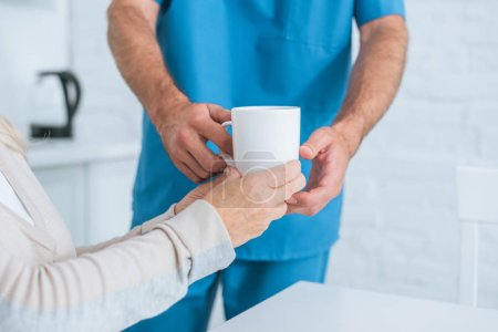 cropped shot of caregiver giving cup of hot beverage to senior woman