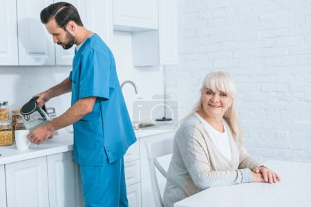 happy senior woman sitting and smiling at camera while caregiver pouring hot beverage in kitchen