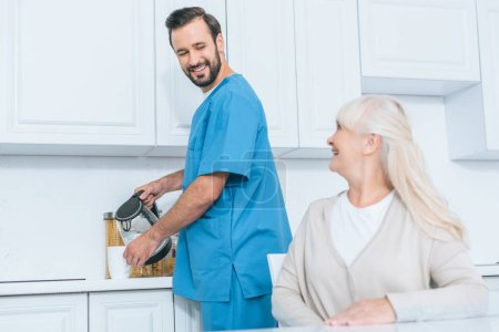 happy senior woman looking at social worker pouring hot beverage in cup