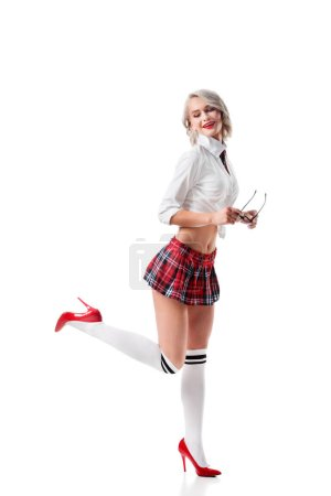 sexy smiling woman in short schoolgirl plaid skirt and knee socks with eyeglasses posing isolated on white