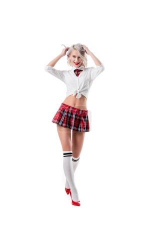 sexy playful woman in short schoolgirl plaid skirt and knee socks with eyeglasses posing isolated on white