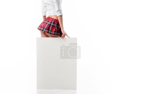 partial view of seductive woman in college uniform standing near blank banner isolated on white
