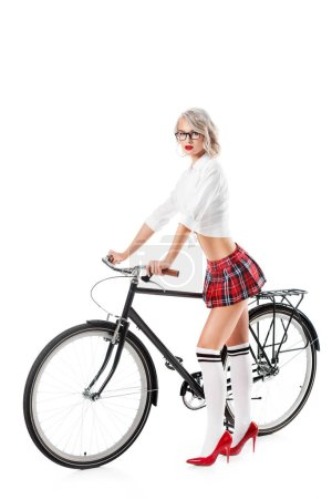 seductive young woman on college uniform with bicycle posing isolated on white
